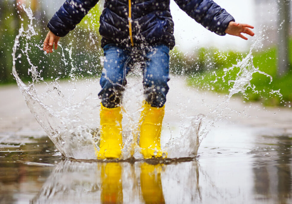 Close up legs of child with yellow rubber boots jump in puddle on an autumn walk